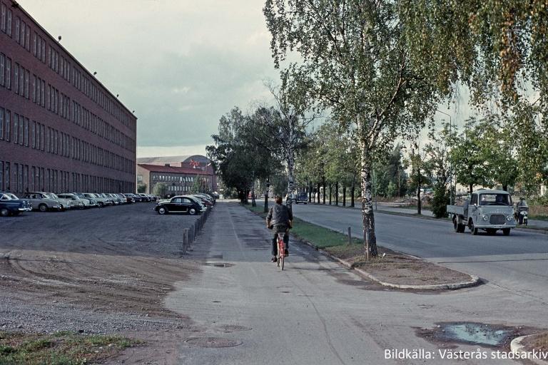 Bild från 70-talet med Navet till vänster och Björnövägen till höger. En man cyklar på cykelvägen mellan huset och bilvägen och tidstypiska bilar står parkerade framför Navet och åker på vägen.