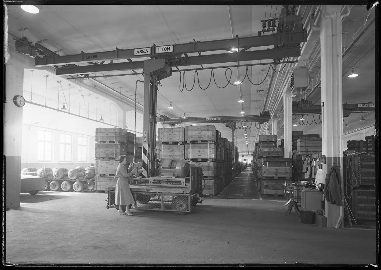Lagerlokal med 1000 kg staplingstravers för hängbana. Viksängshuset D-våningen år 1956. Kvinna packeterar objekt på pall.