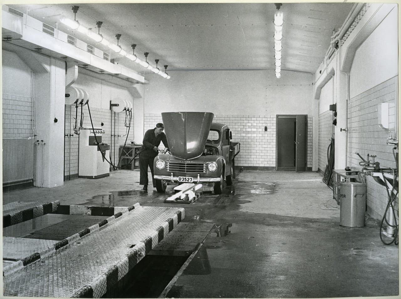 Aseas bilverkstad i Viksängshuset. Smörj- och tvätthallen med hydraliska billyftar år 1956. Man som står och tvättar något under motorhuven på en bil.