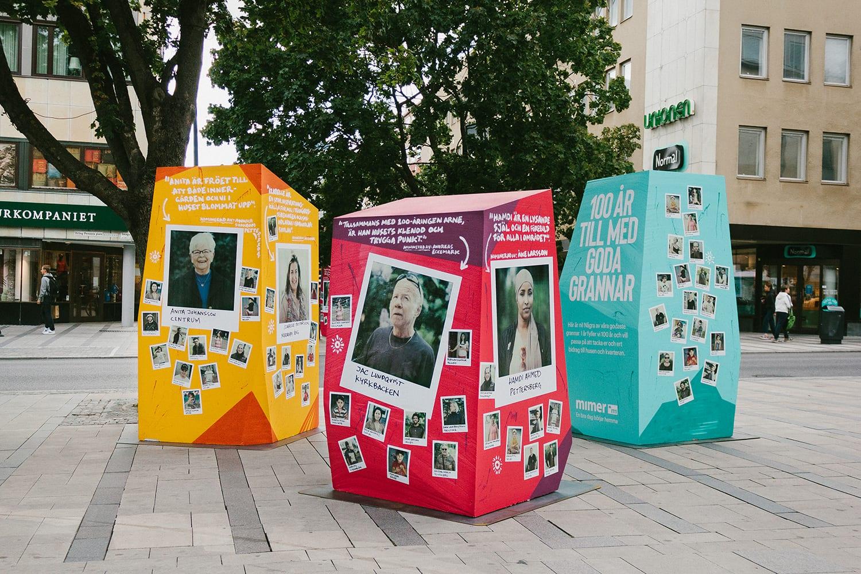 Tre stora kuber i glada färger med foton av och text om personer som är goda grannar.