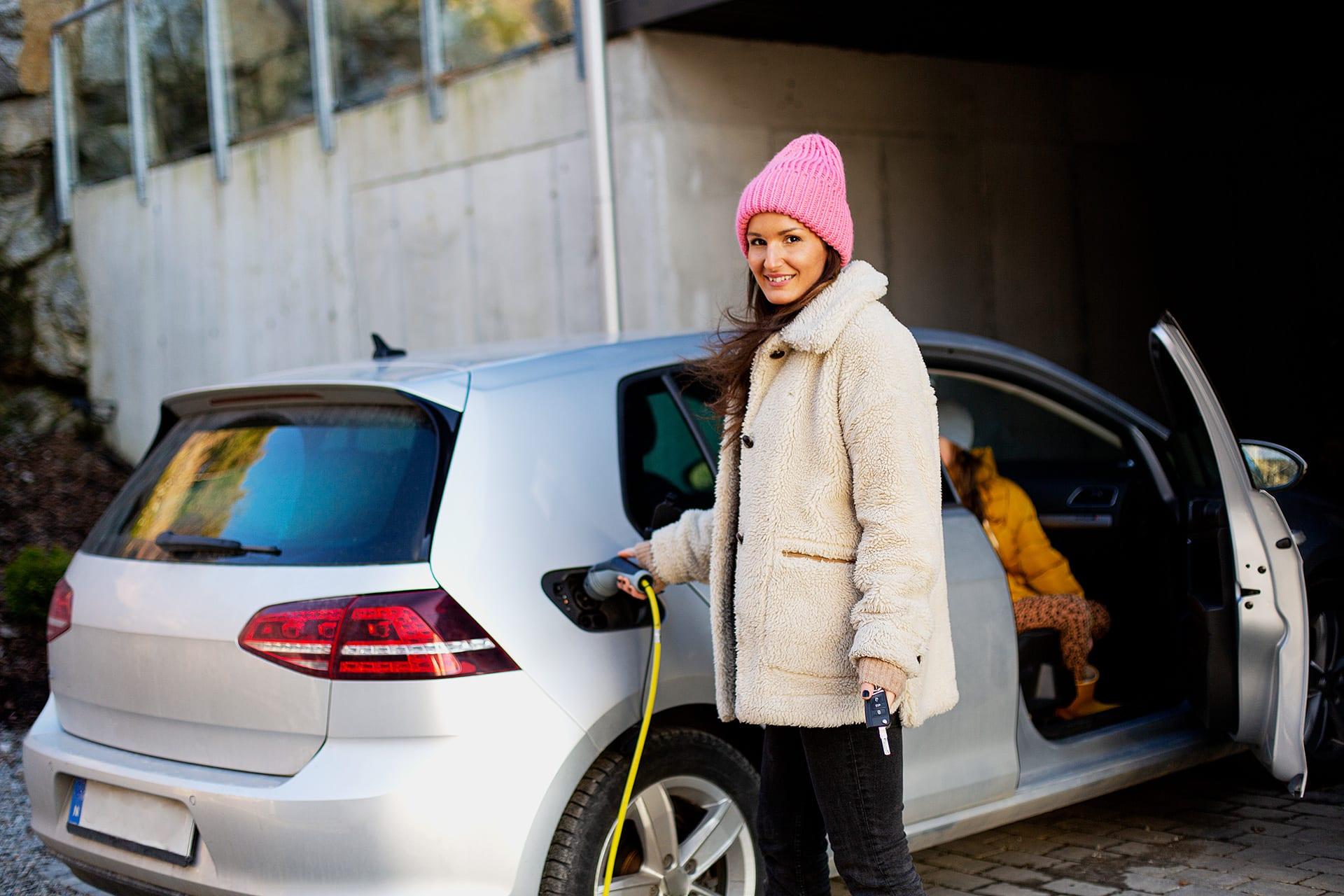 Kvinna laddar en elbil.
